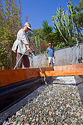 July 24, 2010. Watering the Gypsum for the final preparations of the planting beds at the Venice Community Garden. The Venice Garden broke ground in April, 2010. Soil tests revealed high levels of arsenic and lead because of previous uses which included a railroad line going through the lot. Steps were taken which included adding protective layers and adding new soil. Planting began in August and the first harvest was in October, 2010. Venice, California, USA