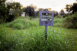 20 August 2015. New Orleans, Louisiana. <br /> Hurricane Katrina revisited. <br /> A forlorn 'No Trespassing' sign is all that stands on an abandoned lot in the still devastated lower 9th Ward. <br /> Photo credit©; Charlie Varley/varleypix.com.