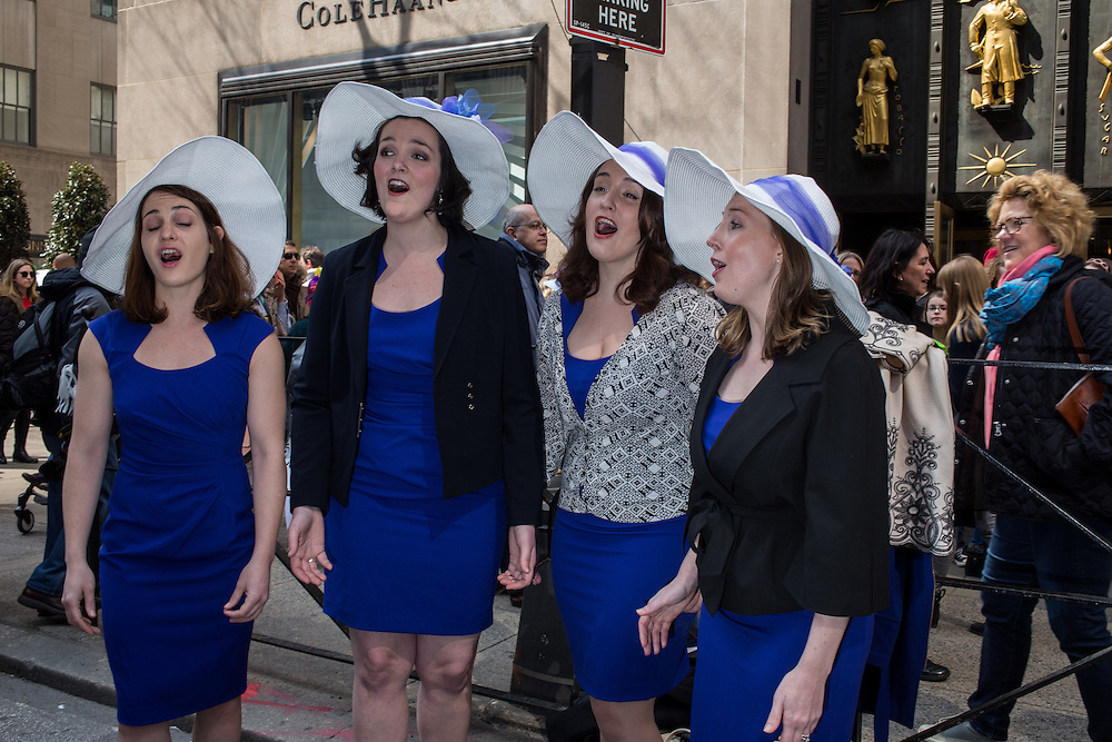 New York, NY, USA-27 March 2016. A quartet of women all in white hats and blue dresses, sing for the crowd in front of Rockefeller Center during the annual Easter Bonnet Parade and Festival.