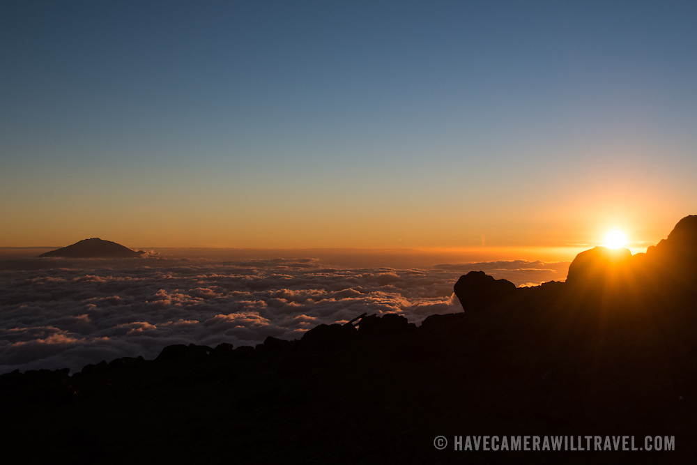 The summit of Mt Meru pokes through the clouds as the sun sets on the horizon as seen from Arrow Glacier on Mt Kilimanjaro's Lemosho Route.