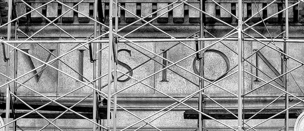 Vision (B&W): Not unlike the normal re-evaluation of a personal perception or understanding; the word Vision is seen through the metal scaffolding during the extensive renovations of the frontal fascia of the Museum of Natural History, New York, New York United States of America.
