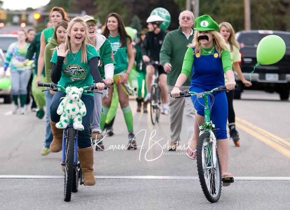 """Seniors Jessie Byran and Stephanie Lund lead their """"Green"""" class representing the United Nations Environment Program down the streets of downtown Laconia during the annual Homecoming Parade Friday evening.  (Karen Bobotas/for the Laconia Daily Sun)"""