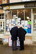 Couple browse the window of a newsagent's shop at Burford in the Cotswolds, United Kingdom