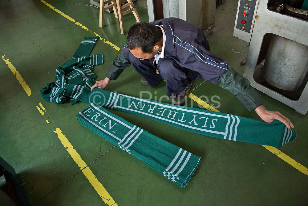 Line worker Wu Xianpin folds Harry Potter Slytherin scarfves at the Yiwu Wells Knitting Products Co., Ltd factory in Yiwu, Zhejiang Province, China on 06 March  2013. The city of Yiwu is known as one of China's largest trading centers for small merchandise and light industry, drawing buyers from around the world. Uncertain global demand, a stronger yuan currency and rising labour costs have taken their toll on Chinese exporters, but analysts believe sales could pick up modestly in 2014 due to improved demand from the United States and Europe.