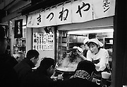 In the Island country of JAPAN, fish and seafood are the central focus of their culinary routine. The Tsukiji  Fish Markets in TOKYO process around 2,700 tons of fish a day handling more than 400 different types of seafood. The bustling marketplace comes to life in the early hours of the morning when the fish is inspected before the auctions start at around 5.30 a.m. Once bought the seafood is taken by the wholesalers back to their stalls in the markets, as well as heading off to restaurants and retailers .Almost all the fish eaten in TOKYO come from these markets. Plans to relocate the markets by 2012 are under way, a move prompted by the ageing buildings of the Tsukiji markets and the larger area of the new site at Toyosu.<br /> <br /> PIXS TAKEN......021221 (21ST DECEMBER 2002)<br /> pic shows .. People eat at the many stalls in and around the markets.