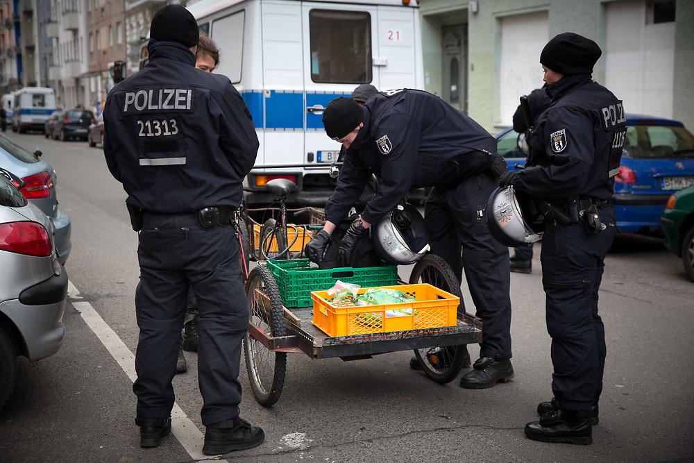 """Protest gegen Razzia in einem Hausprojekt in der Rigaer Strasse und gegen die Einordnung von Teilen des Friedrichshainer Nordkiezes als """"Gefahrengebiet"""". Um die 200 Demonstranten veranstalten einen satirischen """"Gefahrguttransport"""" bis zum Polizeiabschnitt in der Wedekindstrasse. Polizisten durchsuchen mitgebrachtes """"Gefahrgut"""". <br /> <br /> [© Christian Mang - Veroeffentlichung nur gg. Honorar (zzgl. MwSt.), Urhebervermerk und Beleg. Nur für redaktionelle Nutzung - Publication only with licence fee payment, copyright notice and voucher copy. For editorial use only - No model release. No property release. Kontakt: mail@christianmang.com.]"""