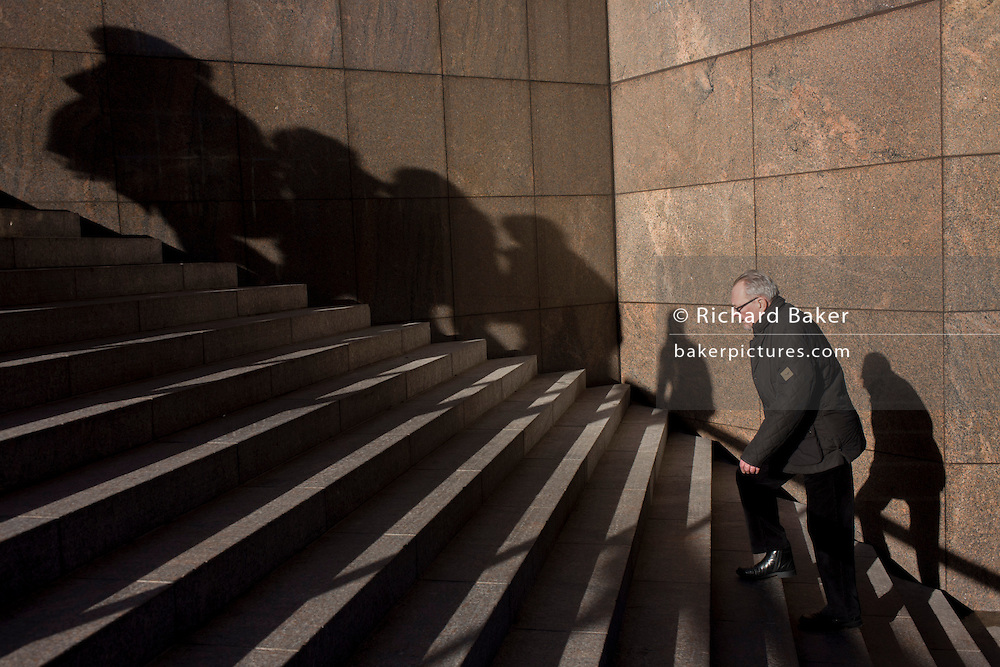 Elderly man struggles up steep steps with the shadows of others on nearby wall.