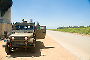 Israel, West Bank, Israeli reserve soldiers on patrol during active duty. Exterior of the armoured jeep. The separation wall on the left