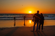 Family watching the sunset, Santa Monica, California, USA