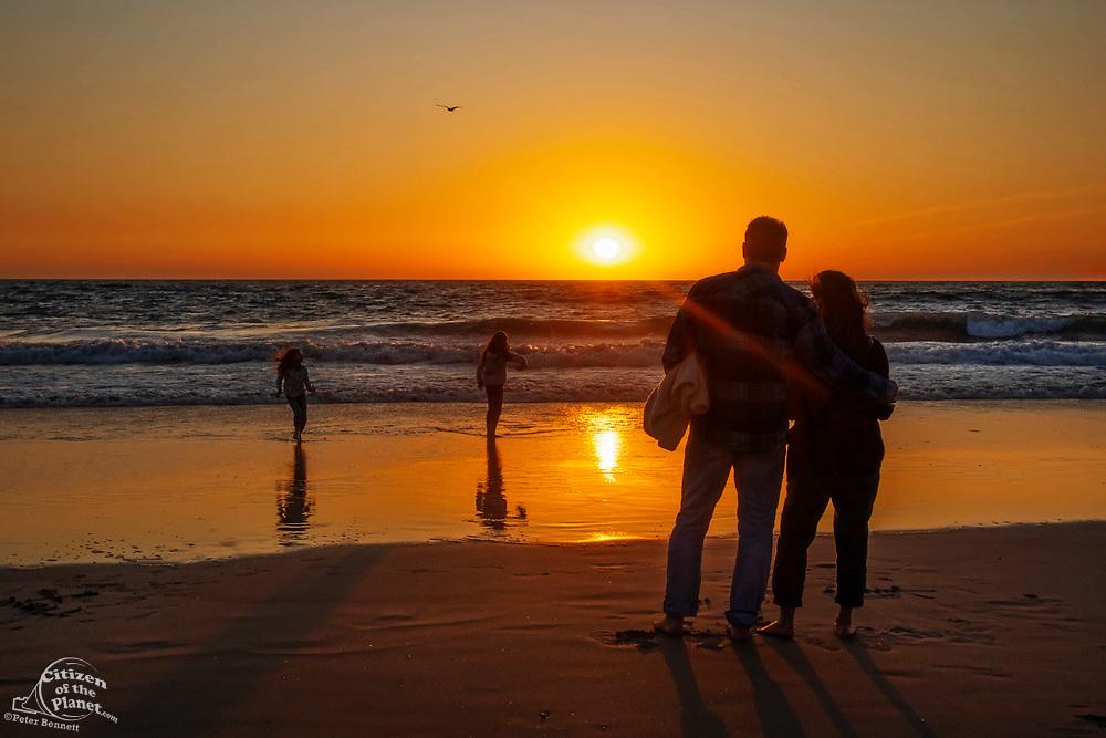 Family watching the sunset, Santa Monica, California, USA