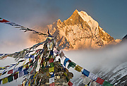 "Machhapuchhre (or Machhapuchhare), the Fish Tail Mountain (22,943 feet / 6997 meters elevation) is a sacred peak, illegal to climb, in the Annapurna mountains (part of the Himalaya range), in Nepal. Tibetan Buddhist prayer flags fly from a monument at Annapurna South Base Camp (ABC, at 13,550 feet elevation) in the Annapurna Sanctuary. Published in Wilderness Travel 2016 Catalog of Adventures and as double page spread inside the cover of Wilderness Travel 2009 Catalog of Adventures, and in 2009 on Swedish travel outfitter web site www.adventurelovers.se. Published in ""Light Travel: Photography on the Go"" book by Tom Dempsey 2009, 2010."