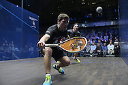 Mathieu Castagnet of France (wearing the black shirt) hitting a shot vs Joe Lee of England (in the grey shirt). Canary Wharf Squash Classic 2016 , day two at the East Wintergarden in Canary Wharf , London on Tuesday 8th March 2016.<br /> pic by John Patrick Fletcher, Andrew Orchard sports photography.