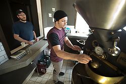 Devout Coffee co-owners Jon Fisher, left, and brother-in-law Stevie Pape prepare to roast another batch of coffee beans, Tuesday, April 5, 2016, in Fremont, Calif. The men started the roastery in their garage, before finding and refurbishing a 1980s-era roaster, and crowd-sourcing their storefront in the Niles neighborhood of Fremont. (Photo by D. Ross Cameron)