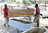 Port-au-Prince, Haiti.  Carpenters move a new coffin to a waiting vehicle in Port-au-Prince, Haiti on Saturday, January 30, 2010. A massive 7.0 earthquake struck the Caribbean island nation on January 12th., killing upwards of 200,000 people.