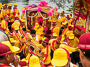 """23 JUNE 2015 - MAHACHAI, SAMUT SAKHON, THAILAND: Men carry the City Pillar Shrine away from a boat on the Tha Chin (Chin River) during the procession for the shrine in Mahachai. The Chaopho Lak Mueang Procession (City Pillar Shrine Procession) is a religious festival that takes place in June in front of city hall in Mahachai. The """"Chaopho Lak Mueang"""" is  placed on a fishing boat and taken across the Tha Chin River from Talat Maha Chai to Tha Chalom in the area of Wat Suwannaram and then paraded through the community before returning to the temple in Mahachai.   PHOTO BY JACK KURTZ"""