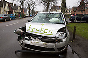 After a recent car crash, a smashed Ford Fiesta with activated airbags is parked on the side of the road awaiting recovery with the word 'Broken' written on the bonnet. Dunfermline, Scotland.