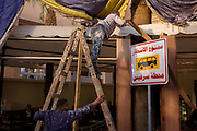 Workmen repair the facade of a restaurant in Luxor, Nile Valley, Egypt. A new bus stop sign in Arabic stands outside the the business as one man up the steps reaches for a length of wooden trim, his mate holds his support to stop them falling, a sign of safety otherwise little understood in an Egyptian city.