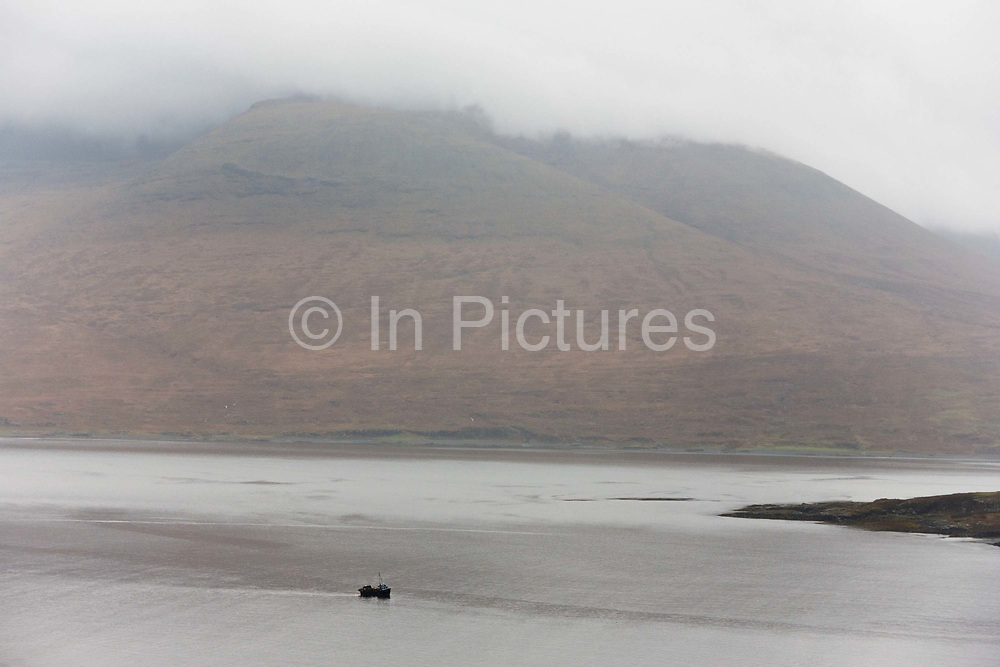 Lone fishing boat makes its way through Loch Na Keal, Isle of Mull, Scotland. The main fishing on the Ross of Mull, Ulva Ferry and Tobermory is now is commercial shell fishing with baited traps (creels) for lobsters (homarus gamarus), edible brown crabs (cancer pagurus), Prawn (Norwegian Lobster) and velvet swimming crab (necora puber). Scallop dredgers and Prawn trawlers also operate from both ends of the island, dragging the seabed for their catch. Before the late 1960s shell fishing with creels was generally carried out on a seasonal or part time basis allied to crofting, farming or another shore based job. Small boats today still operate this way. Loch na Keal National Scenic Area (NSA) embraces the coastline on the West of Mull, from Gribun cliffs to Ulva and Loch Tuath and also includes Inchkenneth, Staffa and the Treshnish Isles.