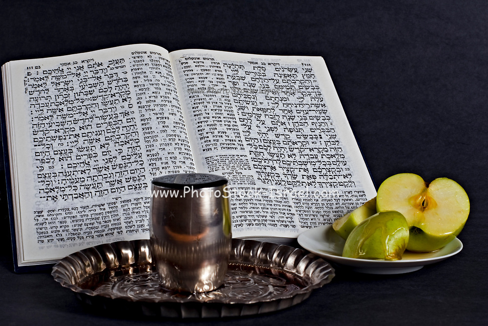 Jewish concept. A still life of a Prayer book, Apple, Honey and a wine goblet