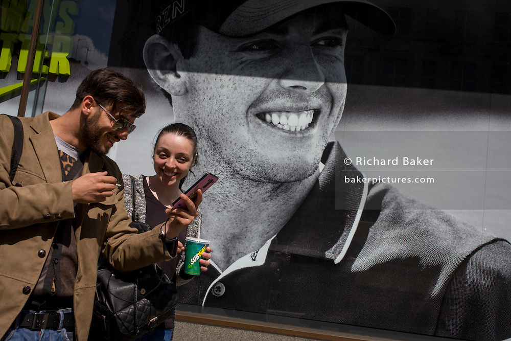 Young smiling couple pass a Nike retail poster of Northern Irish golfer Rory McIlroy, in central London.