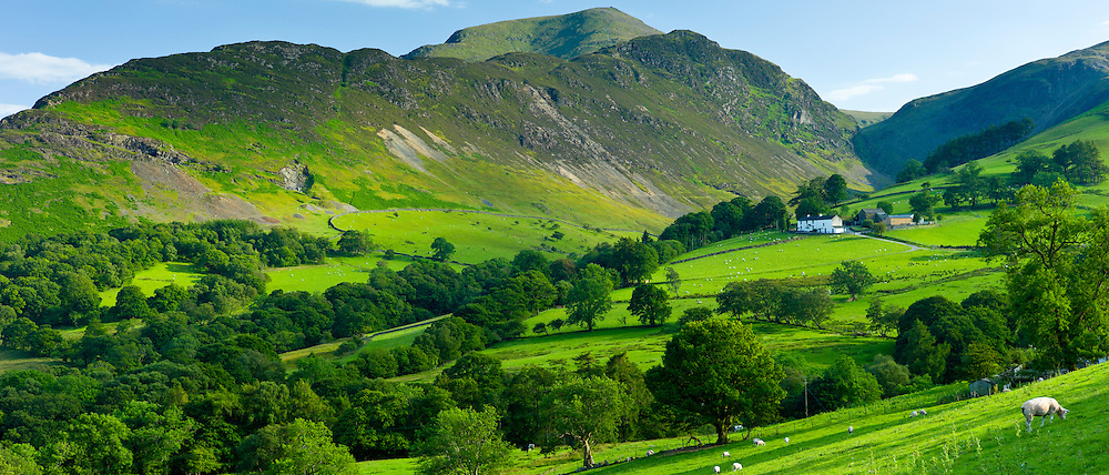 Hill farm in pastureland by Robinson and Scope End Fells, Cumbrian mountains in Lake District National Park, UK