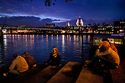 Younng people sitting on the steps leading down to the thames near Blackfriar's bridge. The Thames Festival is an autumn weekend celebration each September on the banks of the river Thames