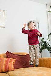 Boy jumping on couch, smiling