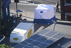 A police officer walks past a forensic tent next to a van in Finsbury Park, north London, where one man has died, eight people taken to hospital and a person arrested after the vehicle struck pedestrians.