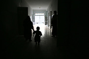 A mother walks with a toddler at the Faizabad Provincial Hospital, Faizabad in Badakshan province, Afghanistan, Saturday, May 12, 2007. Afghanistan has the second highest maternal mortality rate in the world only after Sierra Leone. An astonishing number of 25,000 women die from obstetric causes per year, or 1 woman dies every 27 minutes. A UN report released in 2000 indicates that the national MMR in Afghanistan was 1,900 per 100,000 live births, whereas it was 17 in the United States. Ragh district in Badakshan province showed the highest mortality risk ever recorded in human history, with 64% - more than half of women - of reproductive age died during 1999 and 2002. The causes of deaths were analyzed mainly in two parts: direct and indirect. Direct causes include haemorrhage, obstructed labour, cardiomyopathy, sepsis, obstetric embolism, and pregrancy-induced hypertension; and the indirect causes were tuberculosis, malaria, and obstetric tetanus. Geographical and economical factors also contribute to high mortality in a place like Badakshan where most people have limited access to transportation thus making it harder for women to reach proper health care centers.