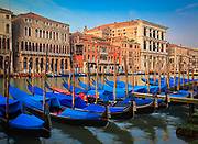"Row of gondolas on Venice's Grand Canal, Italy<br /> .....<br /> Venice is a city in northeastern Italy sited on a group of 118 small islands separated by canals and linked by bridges. It is located in the marshy Venetian Lagoon which stretches along the shoreline, between the mouths of the Po and the Piave Rivers. Venice is renowned for the beauty of its setting, its architecture and its artworks. The city in its entirety is listed as a World Heritage Site, along with its lagoon. Venice is the capital of the Veneto region. In 2009, there were 270,098 people residing in Venice's comune. Although there are no historical records that deal directly with the founding of Venice, tradition and the available evidence have led several historians to agree that the original population of Venice consisted of refugees from Roman cities near Venice such as Padua, Aquileia, Treviso, Altino and Concordia (modern Portogruaro) and from the undefended countryside, who were fleeing successive waves of Germanic and Hun invasions. Some late Roman sources reveal the existence of fishermen on the islands in the original marshy lagoons. They were referred to as incolae lacunae (""lagoon dwellers""). The traditional founding is identified with the dedication of the first church, that of San Giacomo at the islet of Rialto (Rivoalto, ""High Shore""), which is said to have been at the stroke of noon on 25 March 421."