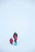 Two children walking with sledge in snow, Nagano, Japan