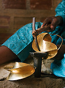 An artisan sculptor shapes metal in his workshop in Djenné, Mali