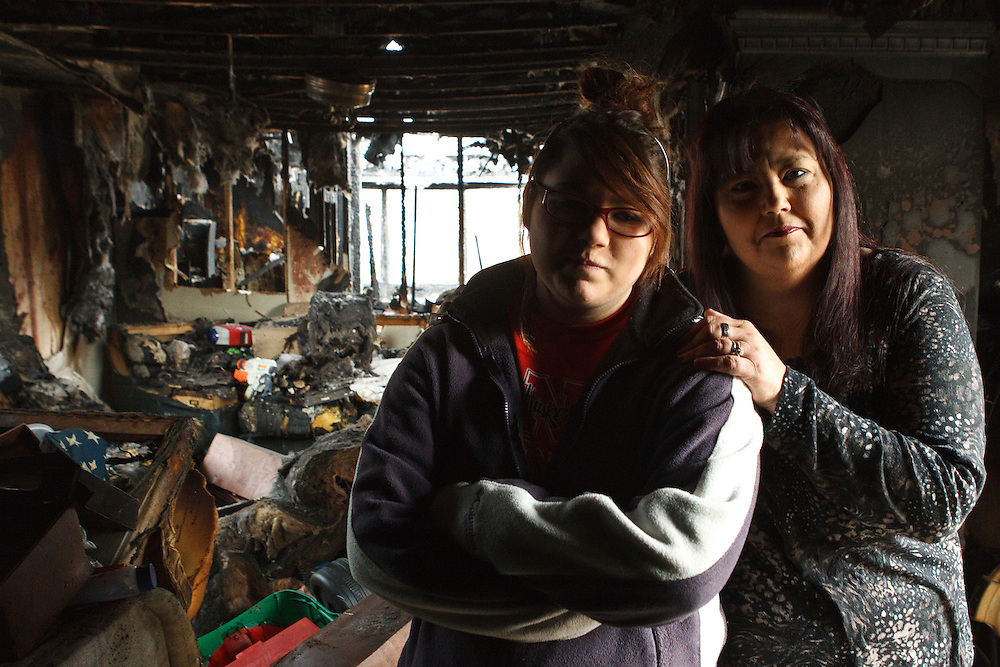 Ashley Toppe and her mother Juanita pose for a portrait inside the burnt remains of what was once their home at West Park Plaza in Grand Island. Juanita and Ashley's 3-year-old son Mateo were at home when the fire started on Nov. 20. Ashley was called out of school at Grand Island Senior High. The fire started in the bedroom behind them at the outlet where the TV was plugged into the wall. (Independent/Matt Dixon)