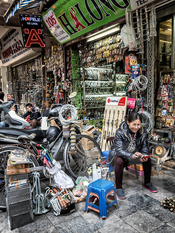 Seller sits beside her shop filled with hardware products along Thuoc Bac street known for hardware goods in Hanoi's Old Quarter, Vietnam, Southeast Asia