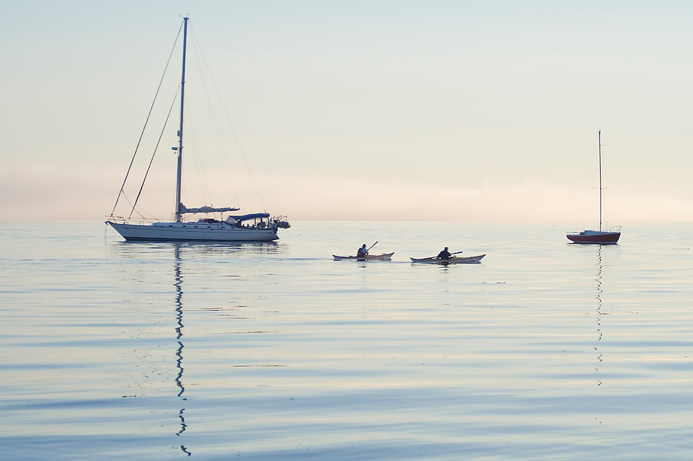 Two kayakers pass by sailboats anchored in Port Angeles Harbor, Washington.