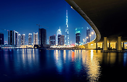 Night view of skyline of new Business Bay District towards Burj Khalifa tower  from The Creek river in Dubai United Arab Emirates