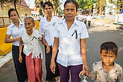03 FEBRUARY 2013 - PHNOM PENH, CAMBODIA:  A Cambodian family leaves the area around the National Museum after visiting the crematorium of former King Norodom Sihanouk. Sihanouk ruled Cambodia from independence in 1953 until he was overthrown by a military coup in 1970. The only music being played publicly is classical Khmer music. Sihanouk died in Beijing, China, in October 2012 and will be cremated during a state funeral royal ceremony on Monday, Feb. 4.    PHOTO BY JACK KURTZ