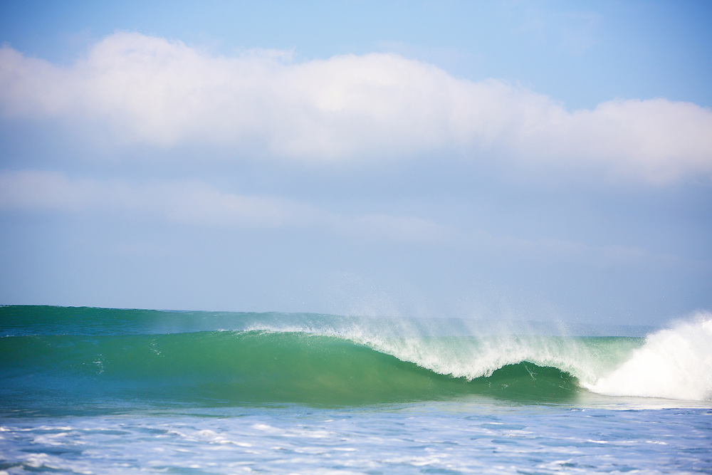 Green and blue waves breaking at St Ouene's Bay, the main surfing beach of Jersey, Channel Islands