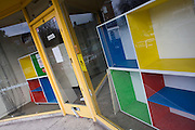 Empty window display of angular coloured shop frontage in London's West Dulwich for a liquidated childrens' clothing shop.