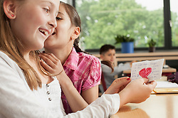 Schoolgirls whispering in classroom and showing a love letter, Munich, Bavaria, Germany
