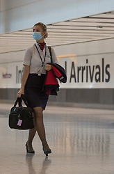© Licensed to London News Pictures.  03/08/2021. London, UK. A stewardess arrives at Heathrow Airport, west London. Fully vaccinated travellers from the United States and much of Europe are able to enter Britain without need to self-isolate, since yesterday. Boris Johnson received a letter from airlines and tour operators calling to simplify rules and drop amber list. Photo credit: Marcin Nowak/LNP