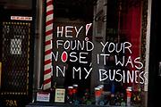 Carter Lane Barbers shop with humourous graffiti written on the window