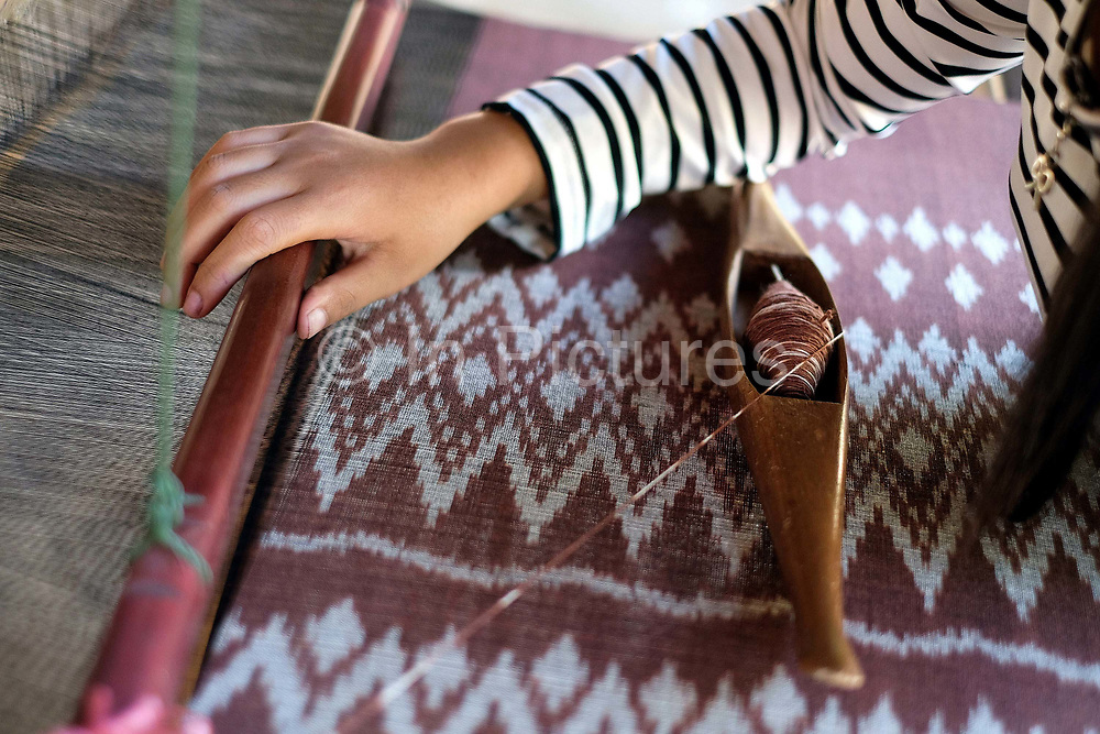 Handweaving organic cotton with a mutmee/tie dye design in Ban Lahanam, Savannakhet province, Lao PDR. In Savannakhet most textiles are dyed with natural dyes according to longstanding traditions. 'Mutmee' is a tie-dye weaving technique that is special to the Phu-Tai ethnic group where the string is tied  in each row wherever the colour is not wanted and then removed after dyeing.