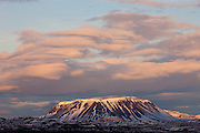 The sunset colors the clouds above Bláfjall, a 1222 meter (4009 foot) table volcano in northern Iceland. Bláfjall formed as a result of an eruption under a thick sheet of ice during the last ice age. Lava forced and melted its way up through the ice and formed a strong shield of lava on the mountain's summit. That strong layer resists erosion, giving the mountain its rectangular shape.