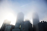 Thick fog over London at the financial district at Canary Wharf making a peaceful yet eerie landscape atmosphere as towers appear and disappear. Modern commercial architecture is releaved through a mist.