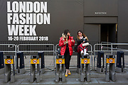 Two stylish women are eating their lunch while perched on empty Santander bike docks on the first day of London Fashion Week in the Strand, on 16th february 2018, in London, England,