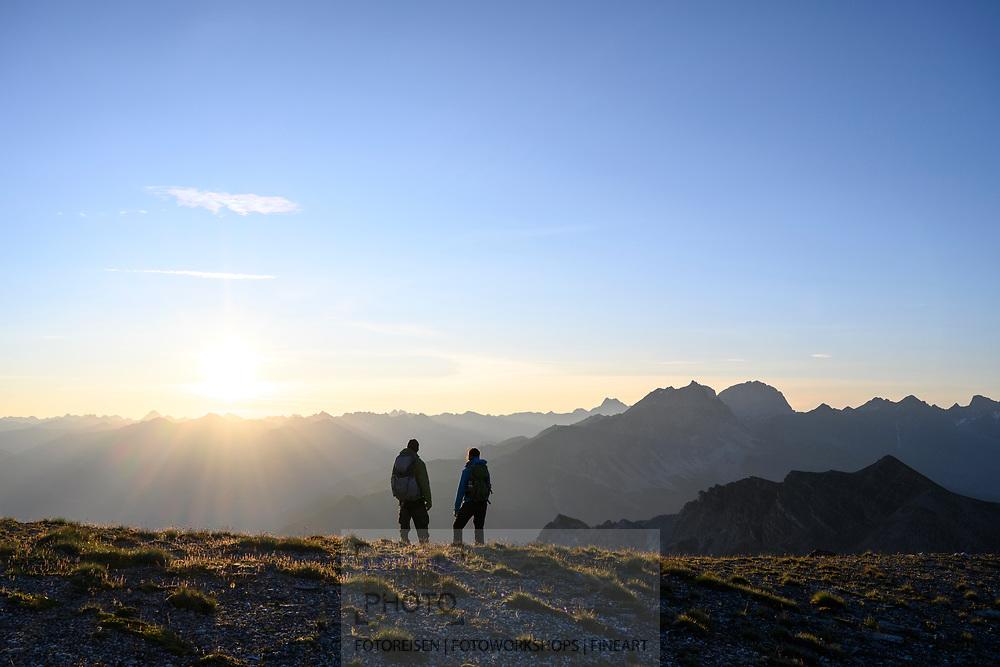 Sonnenaufgang und zwei Wanderer auf einer Wanderung von der Alp da Stierva auf den Curver Pintg mit Blick auf den Piz Toissa und die Bergüner Stöcke mit Piz Mitgel und Piz Ela, Savognin, Parc Ela, Graubünden, Schweiz<br /> <br /> Sunrise and two hikers on a hike from the Alp da Stierva to the Curver Pintg with a view of the Piz Toissa and the Bergüner sticks with Piz Mitgel and Piz Ela, Savognin, Parc Ela, Grisons, Switzerland