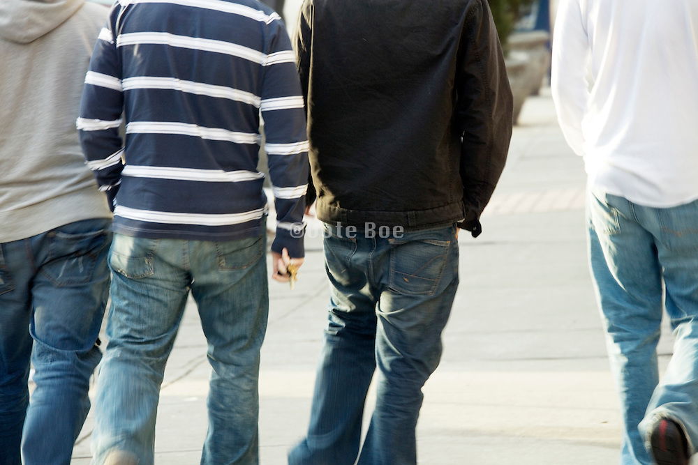 young adult boys walking seen from behind