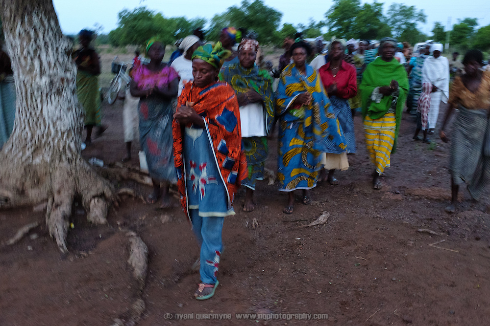 Women singing as darkness falls over the village of Baazing in the Upper West Region of Ghana on 24 June 2015.