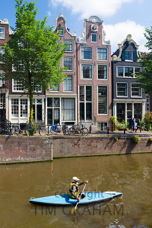 Tourist kayakking in single kayak by canalside gabled houses - Dutch gables - on Brouwersgracht in Amsterdam, Holland